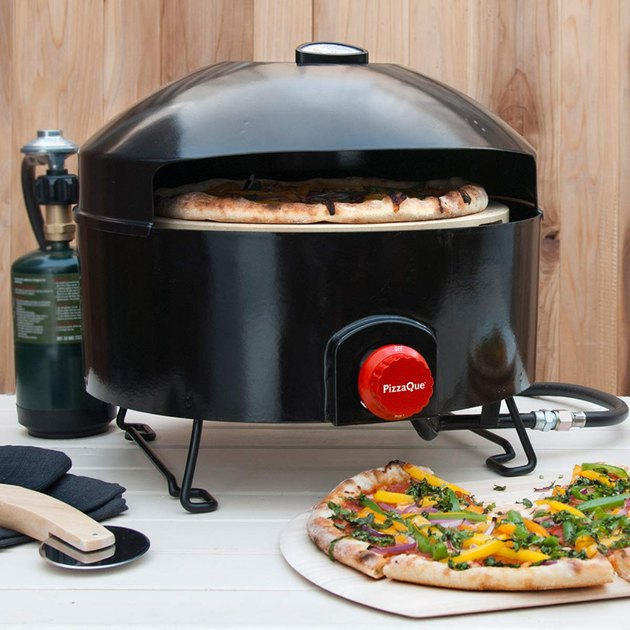 Quality outdoor pizza ovens probably don't come much more affordable than this. It operates on a standard 20-pound propane tank, and comes with the hose needed to get up and running right away. This squat, round oven stands about a foot high and 18 inches in diameter and is open in front (where you'll also find the bright red propane control knob) for sliding your pies in and out. Since it weighs 26 pounds, this oven is fairly portable; pack it and a standard propane tank in the back of your car for a camping trip, and Pizzacraft says you can make more than 200 pizzas.