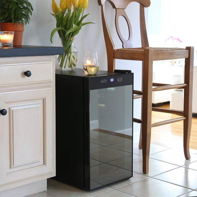 If you have an extra sunny kitchen or live somewhere with year-round sunshine, this single-zone wine cooler is your best bet. It has a fairly conservative look thanks to the simple smoked glass door and a simple temperature display and minimal touch controls at the top, but the frosted glass is built to block out harmful UV rays that can damage the wine. It holds 18 bottles and is billed as a countertop model, but since it stands about 25 inches high, you'll likely have to set it on the floor. The shelves are designed to slide out for easy access to your wine collection.