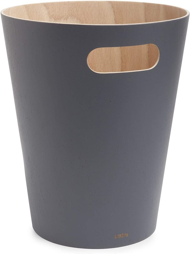 With clean lines and a matte finish, the Umbra Woodrow Wastebasket adds a modern touch to any space. It has a natural wood interior, built-in handles, painted exterior, and two-gallon capacity.
