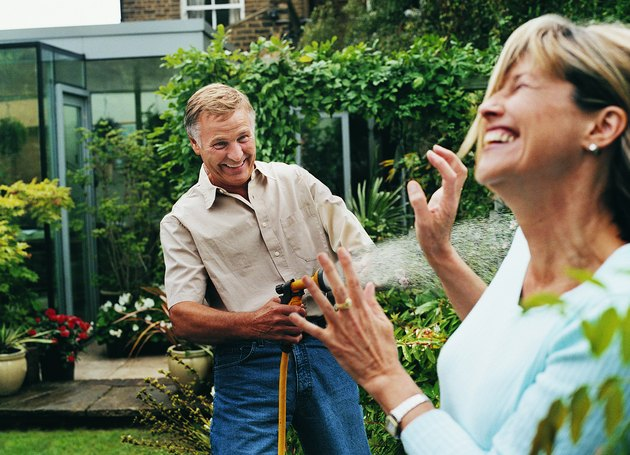 Mature Man Spraying a Woman With Water From His Garden Hose
