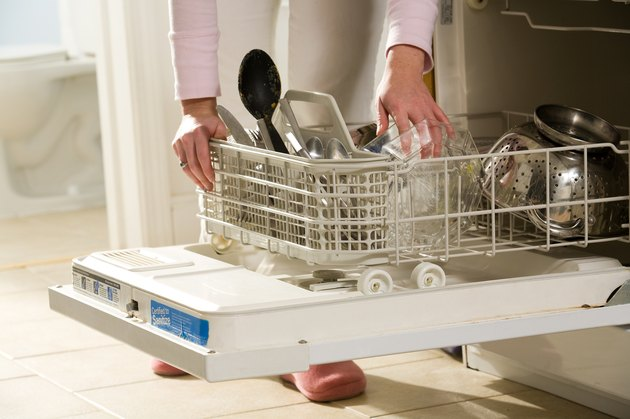 Woman arranging silverware in dishwasher