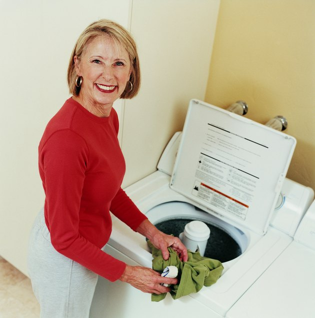 Portrait of a Mature Woman Loading a Washing Machine
