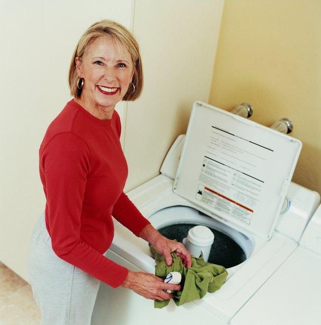 Portrait of a Mature Woman Loading a Washing Machine