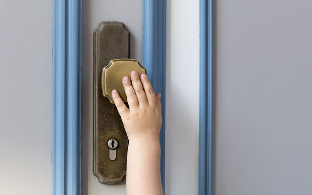 Little child hand on the door handle