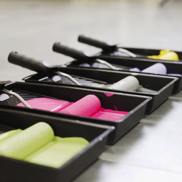 Close-up side view of trays of coloured paint and paint rollers