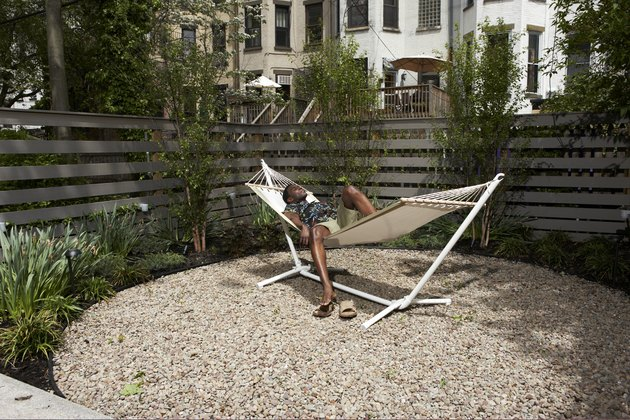 Man relaxing in urban backyard hammock