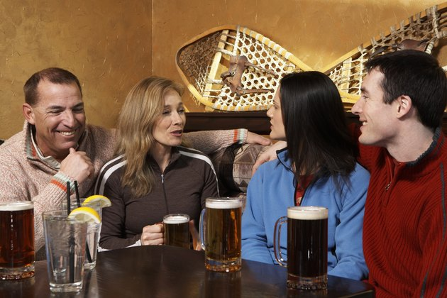 Four adults drinking beer and talking in pub
