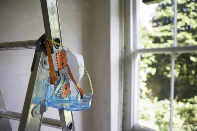 Protective safety goggles and dust mask hanging from step ladder
