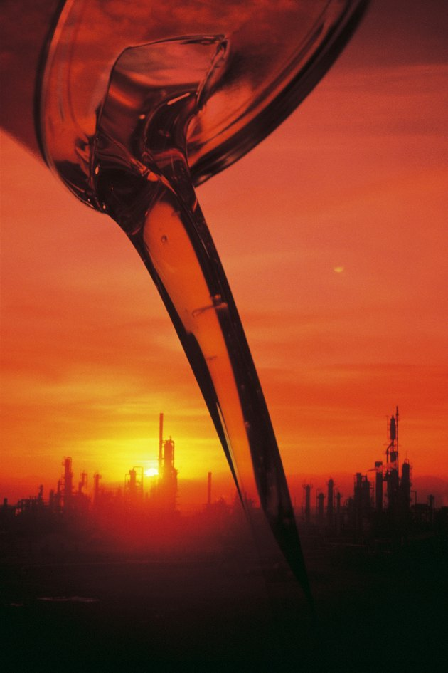 Oil pouring from a container , image of refinery background