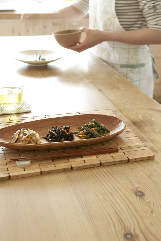 Japanese style vegetables in wooden tray with chopsticks on wooden table, woman preparing food in background