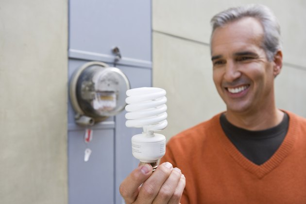 Man with home electric meter and compact fluorescent light bulb