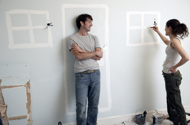 Couple painting doors and windows on an old wall
