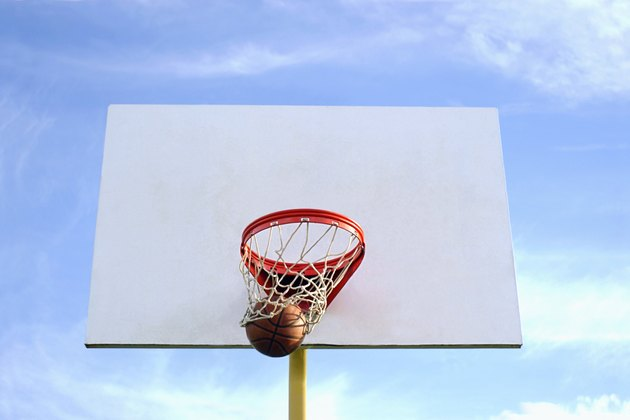Low angle of a basketball going through the net.