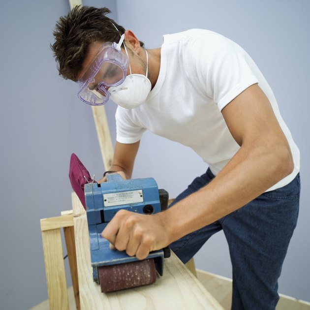 young man leveling a plank of wood with an electric sander