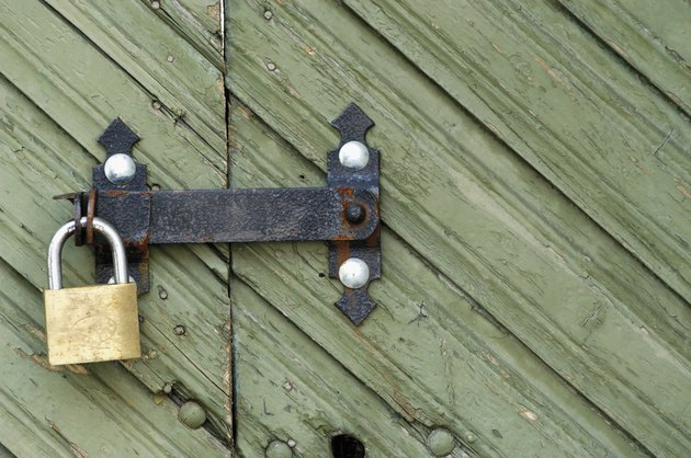Close-up of a wooden door with a padlock