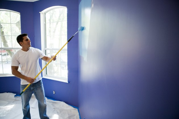 Young man painting wall with paint roller in house