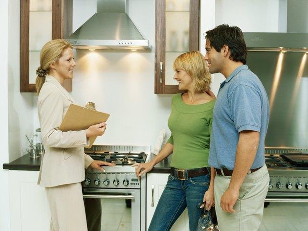 Female salesclerk demonstrating cooker to couple, smiling