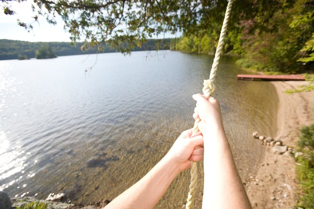 Hands gripping rope swing on shore of lake