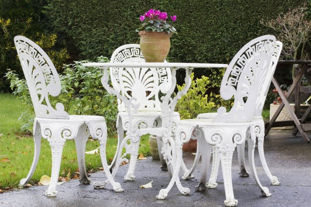 White-painted, decorative garden furniture on patio, including four chairs and plant in terra cotta pot in center of table