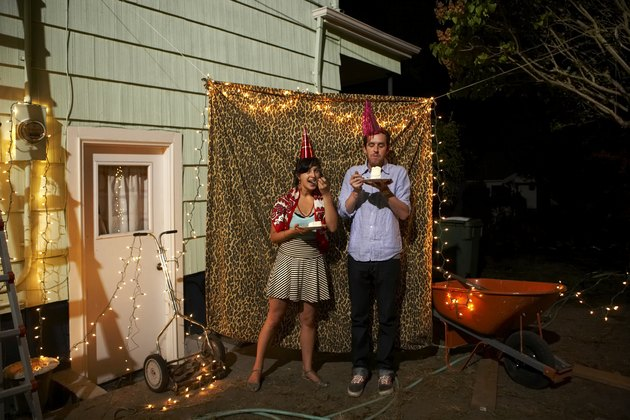 Young couple standing by leopard curtain at party