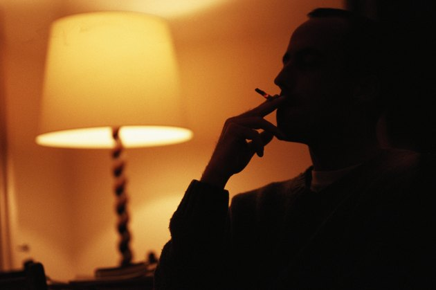 Man smoking by electric lamp, silhouette