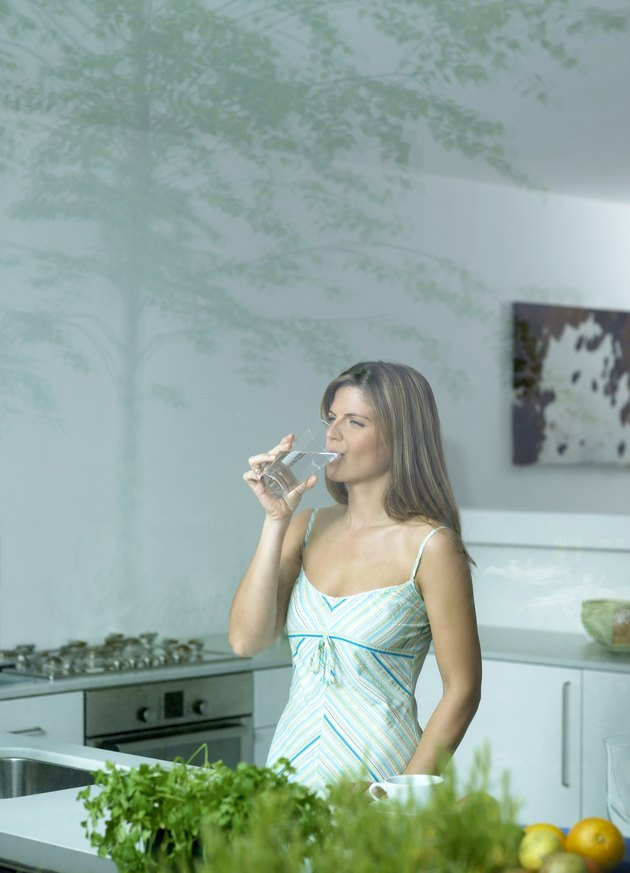 Woman drinking glass of water in kitchen, view through window
