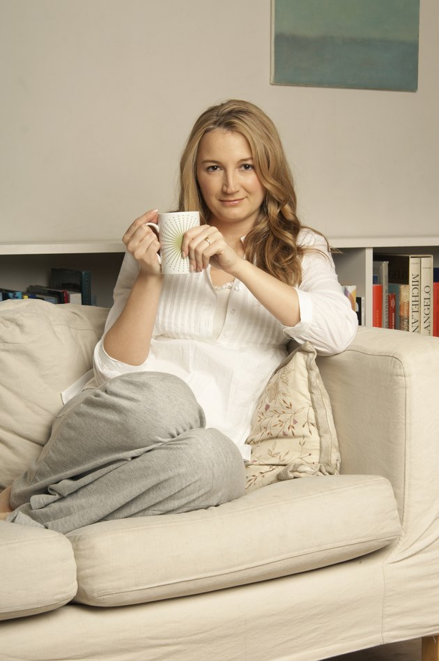 Young woman with mug sitting on sofa, portrait