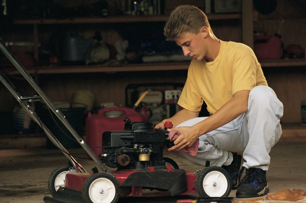 Teenage boy fixing lawnmower