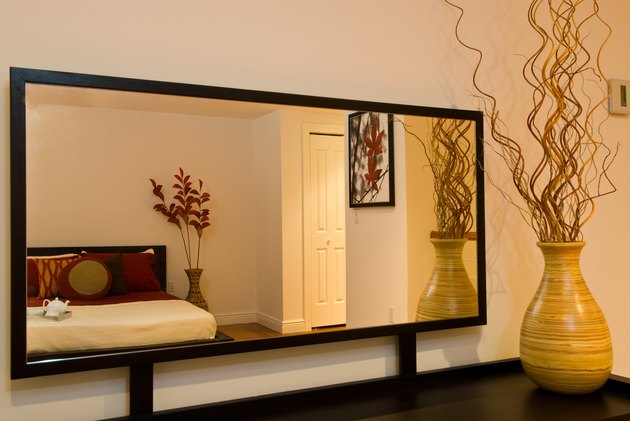 Reflection of bed in bedroom mirror