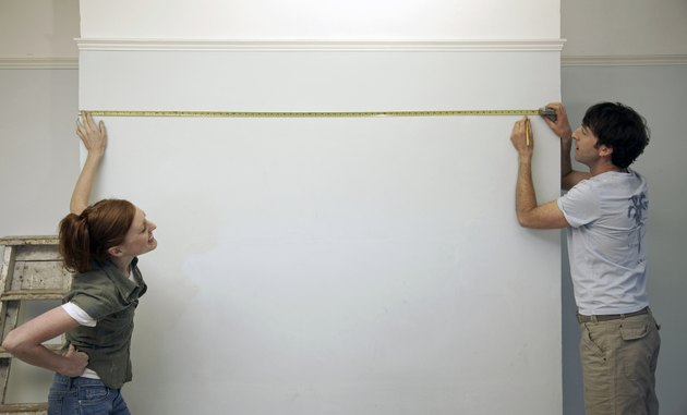 Couple measuring and marking a wall