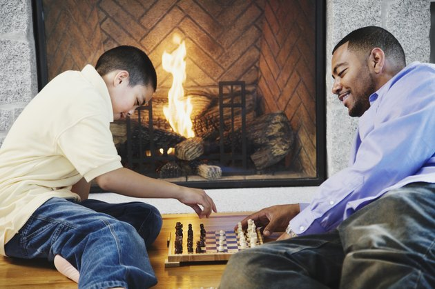 Father and son playing chess by fireplace