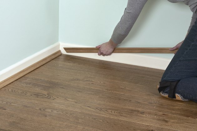 Man using hands to position edging bead at edge of laminate floor and skirting board
