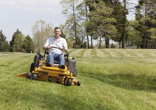 Senior man rides zero turn lawn mower on turf