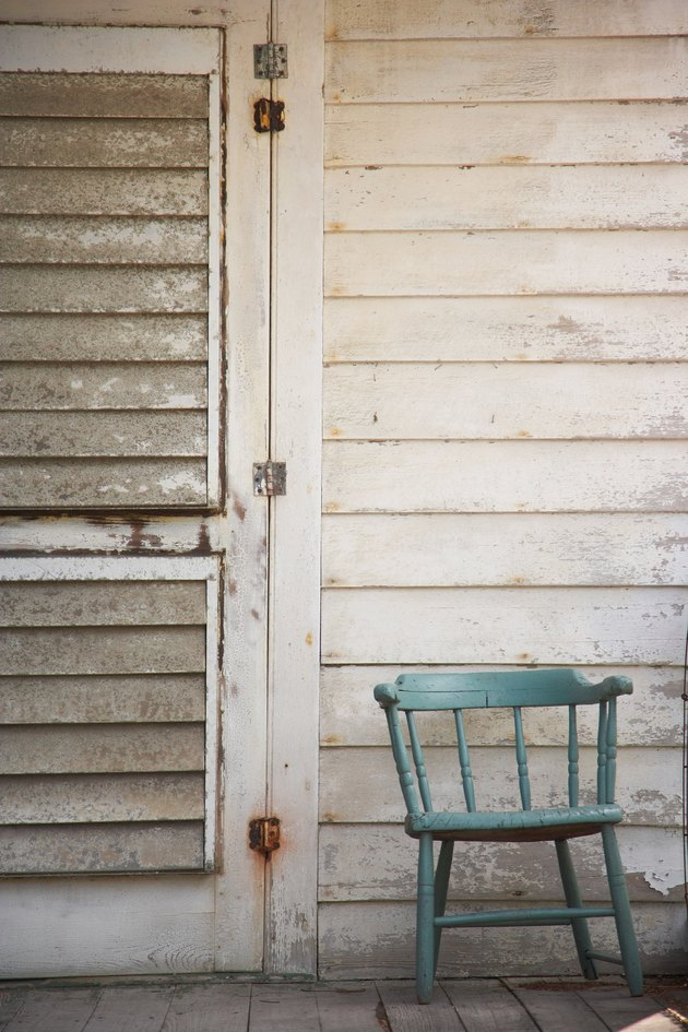 Chair on porch of weathered and derelict house
