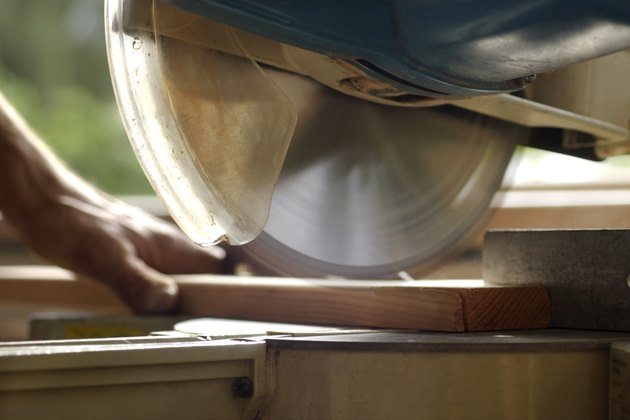 Close-up of circular saw blade in motion as a man is about to cut a piece of wood.