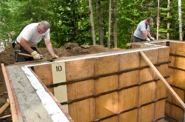 Two construction workers smoothing concrete in wall molds