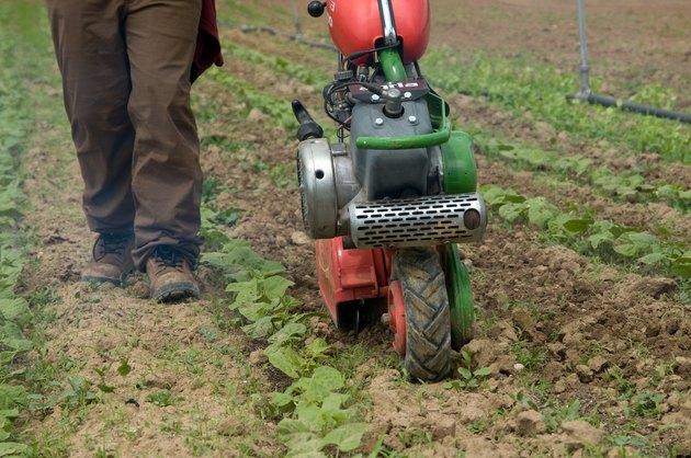 Farmer tilling soil with rototiller