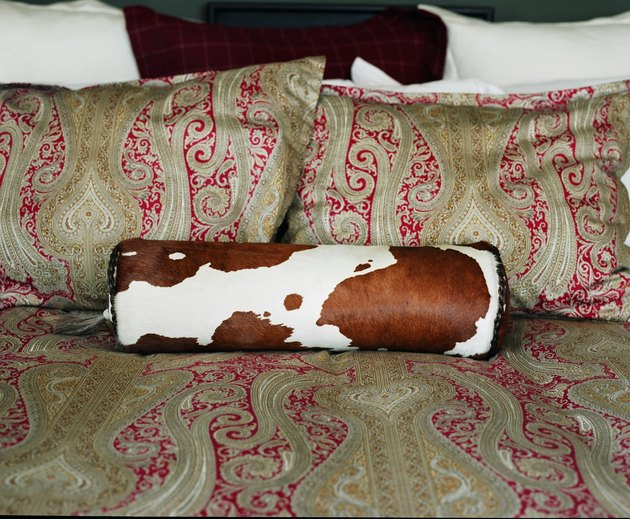 Paisley pattern of bed and pillows with roll cushion in cowhide