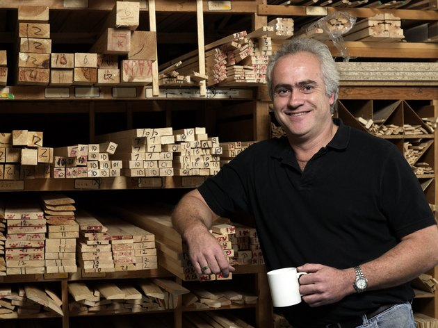 Man by planks of wood on shelves holding mug, smiling, portrait