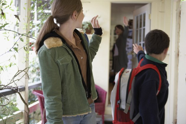 Close-up of a teenage girl and her brother waving at their mother while going to school