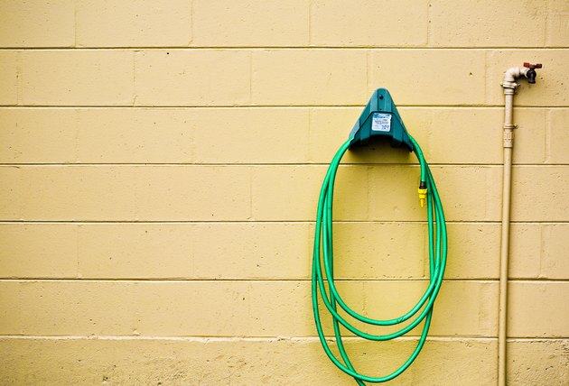 Garden hose in rack on wall with faucet
