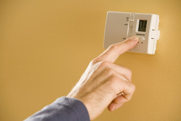 Person adjusting thermostat