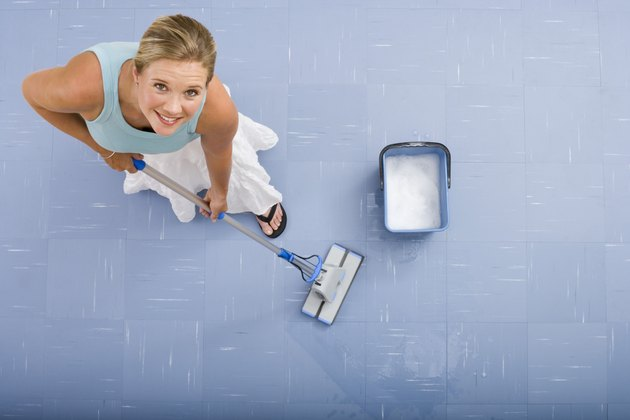 Woman mopping with mop and bucket