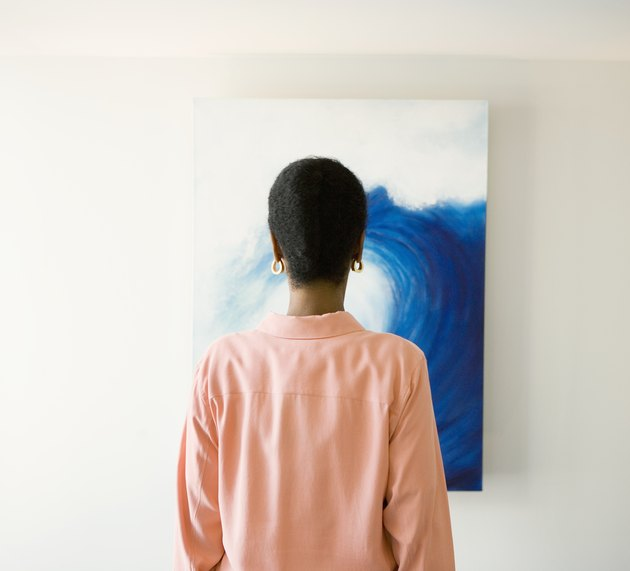 African woman looking at painting