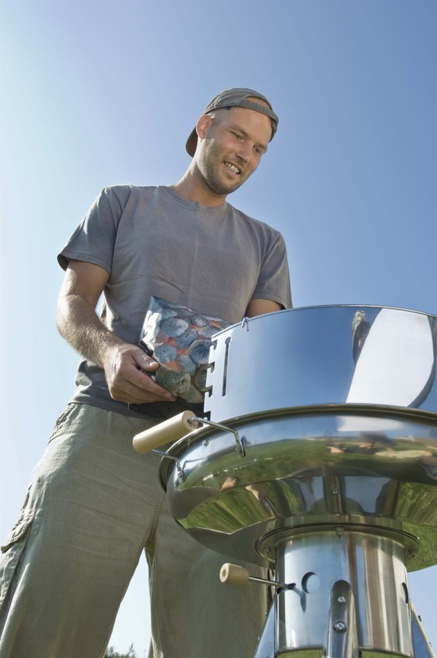Man pouring charcoal into grill