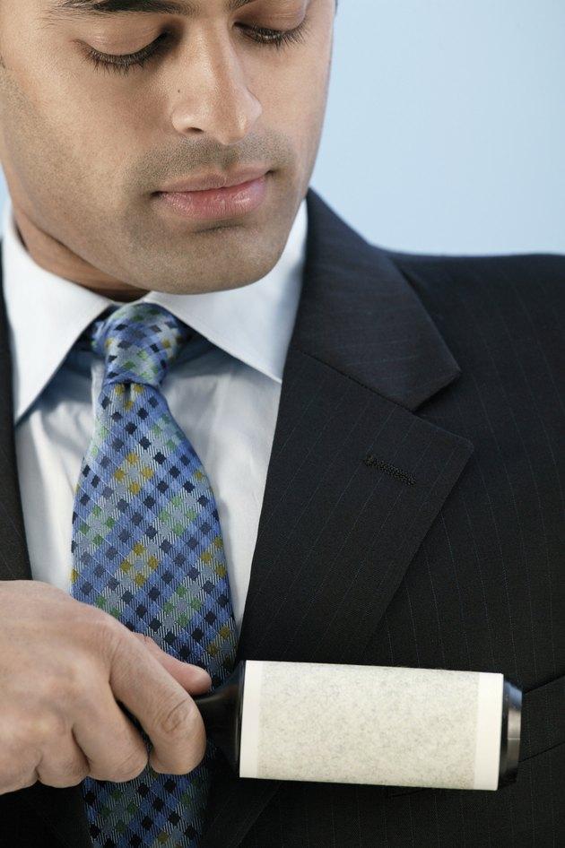 Businessman using lint roller
