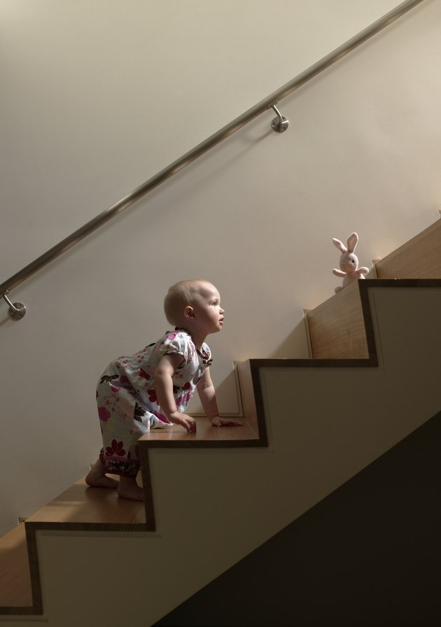 Baby girl climbing stairs to get toy