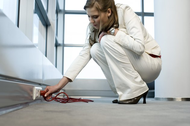 Businesswoman plugging in electrical cord