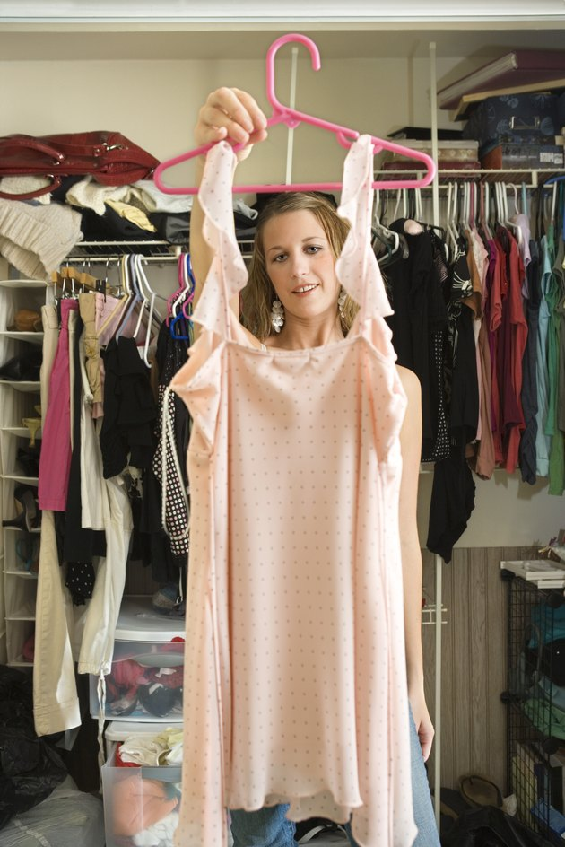 Woman holding up clothes in closet
