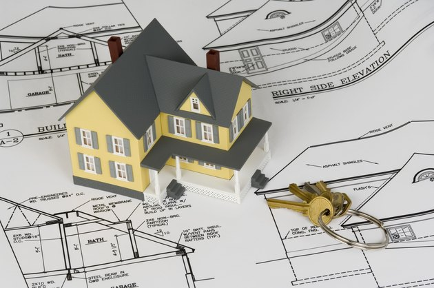 Miniature house with keys and blueprints